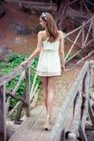 Härlig kvinna med långa ben som bär den vita klänningen som går på bron i skogen Arkivbilder