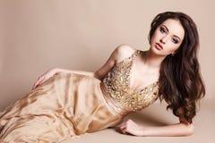 Härlig kvinna med mörkt hår i lyxig siden- klänning Royaltyfri Foto