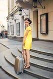 Härlig kvinna med resväskan på ingången till hotellet Arkivfoton
