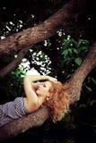 Härlig kvinna på en förgrena sig av treen Royaltyfri Bild