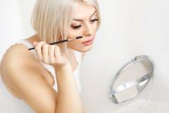 Härlig kvinna som applicerar mascara på ögonfrans. Ögonmakeup Arkivbilder