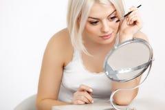 Härlig kvinna som applicerar mascara på ögonfrans. Ögonmakeup Royaltyfri Foto