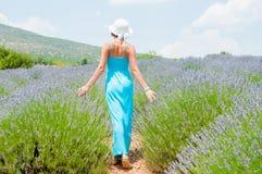 Härlig kvinna som bara går i lavanderfält Arkivfoto