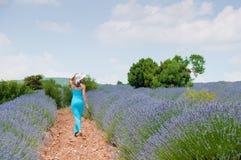 Härlig kvinna som bara går i lavanderfält Arkivbild