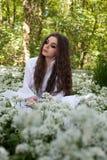 Härlig kvinna som bär ett långt vitt klänningsammanträde i en skog Fotografering för Bildbyråer