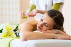 Kvinna som har wellnessbaksidamassage i brunnsort Royaltyfri Fotografi