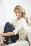 Härlig kvinna som kramar knä, medan sitta på soffan Royaltyfria Foton