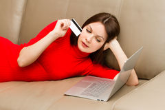 Härlig kvinna som ligger på soffan med bärbara datorn. Arkivbilder
