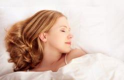 Härlig kvinna som netto sovar i vitsäng Fotografering för Bildbyråer