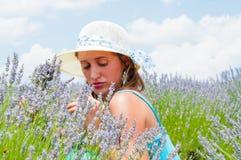 Härlig kvinna som poserar i lavanderfält Arkivbild