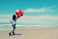 Härlig kvinna som rymmer röda ballonger Arkivfoton