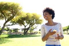 Härlig kvinna som utanför lyssnar till musik på den smarta telefonen Fotografering för Bildbyråer