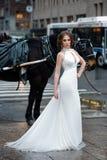Härlig kvinnabrud i den långa vita bröllopsklänningen som poserar i den New York City gatan Fotografering för Bildbyråer