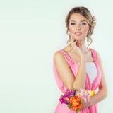 Härlig kvinnaflicka som en brud med den ljusa makeupfrisyren med blommarosor i huvudet i en rosa klänning Royaltyfria Foton