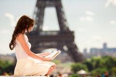 Härlig kvinnaläsebok i Paris bakgrund Eiffeltorn Arkivbild