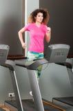 Härlig kvinnaspring på trampkvarnen i idrottshallen Arkivbild