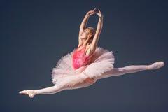 Härlig kvinnlig balettdansör på en grå färg Arkivbilder