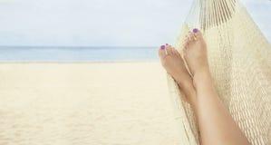 Härlig kvinnlig fot som kopplar av i en hängmatta på stranden Arkivbild