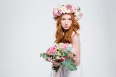 Härlig kvinnlig i krans av rosor som poserar med blommabuketten Arkivbilder