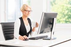 Härlig kvinnlig kontorsarbetare som har ett avbrott vid datoren som har en kopp kaffe Fotografering för Bildbyråer