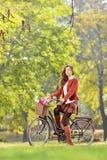 Härlig kvinnlig på en cykel i en parkera Royaltyfri Bild