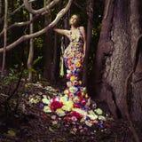Härlig lady i klänning av blommor Fotografering för Bildbyråer
