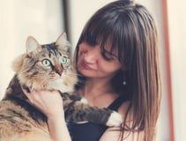 Härlig le brunettflicka och hennes ljust rödbrun katt Arkivbilder