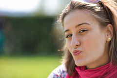 Härlig le flicka som överför dig en kyss Arkivfoto