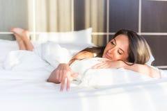 Härlig le kvinna som ligger i hennes sovrum Arkivfoton