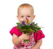 Härlig liten flicka med en liten bukett av blommor Arkivfoton
