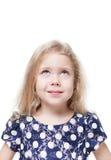 Härlig liten flicka som ser upp på isolerad något Arkivfoton