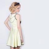 Härlig älskvärd försiktig elegant ung blond kvinna i en gul sommarklänning med pricheskoyiblommakransen i hennes hår Royaltyfri Bild