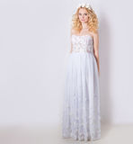 Härlig älskvärd försiktig elegant ung blond kvinna i en vit sundresschiffong och krullning och en krans av blommor i hennes hår Royaltyfri Foto