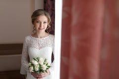 Härlig lycklig brud med bröllopblommabuketten i den vita klänningen med bröllopfrisyren och makeup Royaltyfri Fotografi