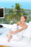 Härlig lycklig kvinna på den vita soffan Arkivbilder
