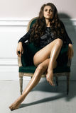Härlig lyxig kvinnamodell som poserar i svart spets- klänning i rertrostol Härlig stående i inre Royaltyfria Bilder