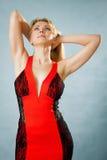 Härlig modekvinna som poserar i röd klänning Arkivbild
