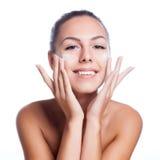 Härlig modell som applicerar kräm- behandling för skönhetsmedel på hennes framsida på vit Royaltyfri Foto