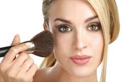 Härlig modell som applicerar yrkesmässigt smink genom att använda en borste Arkivfoto