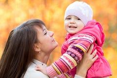 Härlig moder med ungeflickan utomhus i nedgång Arkivbild