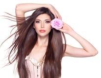 Härlig nätt kvinna med den långa hår- och rosa färgrosen på framsidan Arkivfoto