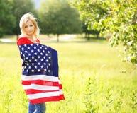 Härlig patriotisk ung kvinna med amerikanska flaggan Arkivbilder