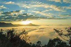 Härlig resningsol i ottan över havet av dimma på kullen av Phu Tok Arkivfoton