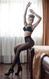 Härlig sexig blond ung kvinna som bär svart damunderkläder, behån och strumpbyxor som sitter på säng Trendig kvinnlig med den att Royaltyfri Bild