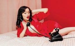 Härlig sexig kvinna som ligger på sängen med telefonen Royaltyfri Fotografi
