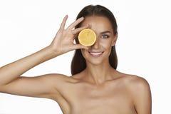 Härlig sexig ung kvinna med perfekt sund hud och skuldror för lång brun hårdagmakeup som kala rymmer den orange citrongrapefrukte Royaltyfri Foto
