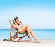 Härlig, sportig och sexig kvinna som kopplar av på stranden Arkivfoton