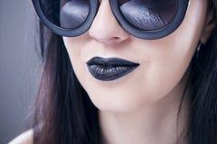 Härlig stående för kvinnamodemodell i solglasögon med svarta kanter och örhängen Idérik frisyr och smink Arkivbilder