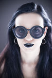 Härlig stående för kvinnamodemodell i solglasögon med svarta kanter och örhängen Idérik frisyr och smink Royaltyfria Bilder