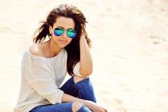 Härlig stilfull kvinnlig i solglasögon som sitter på en strand Royaltyfri Fotografi